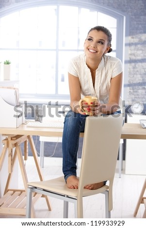 Attractive young girl daydreaming, sitting on top of desk, drinking tea.