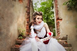Attractive young girl dressed as red queen medievel costume outdoors