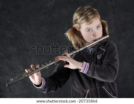 Attractive young girl flautist, flutist holding flute. Studio shot, black background.