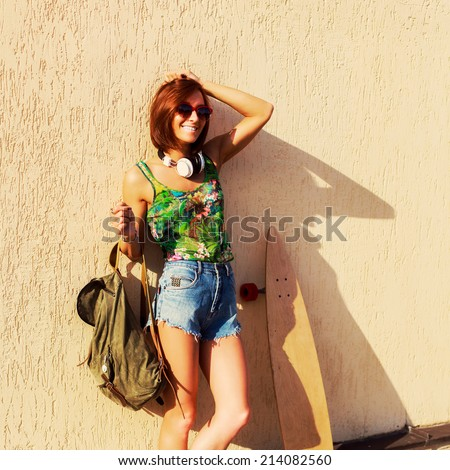 Attractive young girl hipster posing by the wall in summer hot weather with travel bag and longboard . Not isolated. Indoor