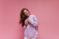 Attractive young girl in oversized sporty outfit smiles widely. Charming brunette woman in hoodie poses on pink isolated background.