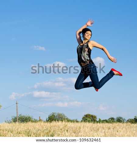 Attractive young girl jumping on the field.