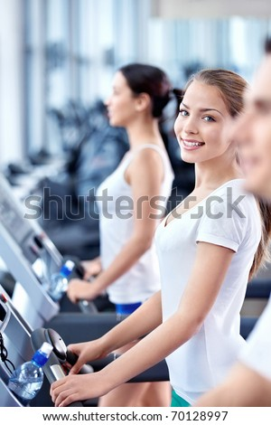Attractive young girl on a treadmill in fitness club