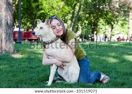 Attractive young girl playing with dog. Outdoor