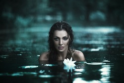 Attractive young girl posing in a river. Grain added