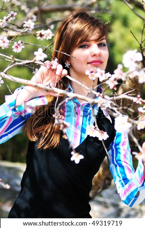 attractive young girl standing with first spring flowers of sakura - stock photo