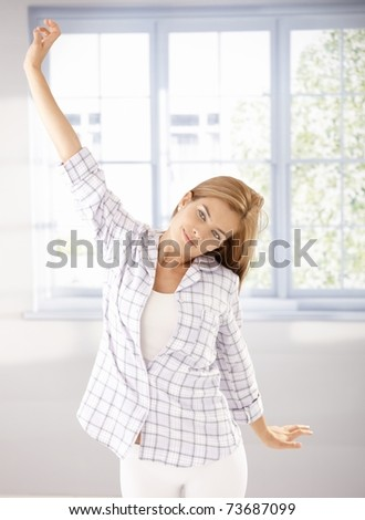 Attractive young girl stretching in the morning at home in pyjama.?
