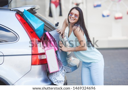 Attractive young girl trying to put a lot of retails into a car. Woman putting shopping bags into a luggage. Young female shoving up her shopping bags into a trunk. Foto stock ©