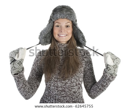 Attractive young girl wearing a warm sweater, fur hat and mittens