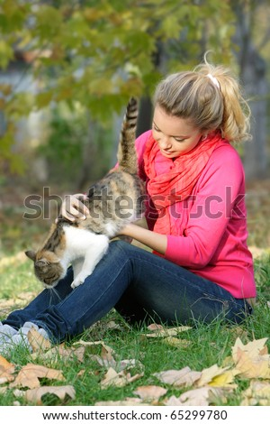 attractive young girl with cat outdoors