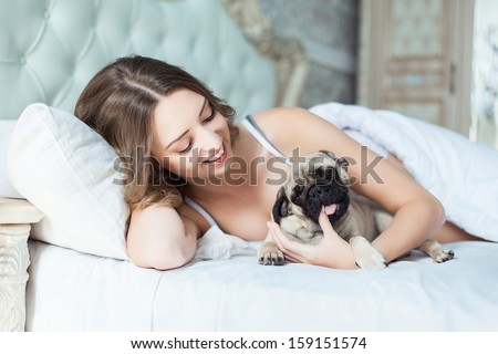 Attractive young girl with dog while laying on a bed