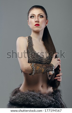 Attractive young girl with long hair in a chain-mail shirt #177194567