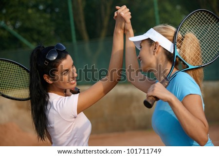 Attractive young girls shaking hands on tennis court, smiling.