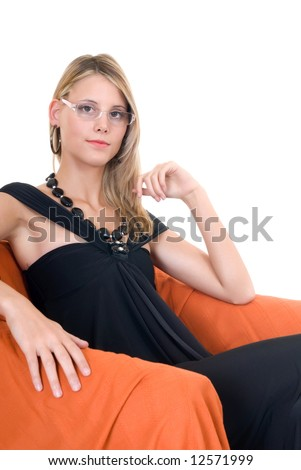 Attractive young glamor lady in arm chair with classy, evening dress.  Studio shot, white background.