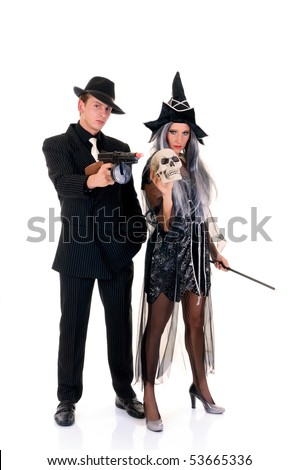 Attractive young Halloween couple, mafia suit and witch costume.    Studio shot, white background. - stock photo