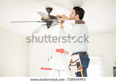 Attractive young handyman stepping on a ladder and fixing a ceiling fan #738964993