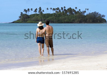 Attractive young happy couple on vacation looks at small Pacific Island. Concept photo of couples travel ,tourism, love, relationship, honeymoon.