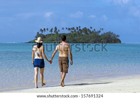 Attractive young happy couple on vacation walks on a beach of Pacific Island.Concept photo of couples travel ,tourism, love, relationship, honeymoon.