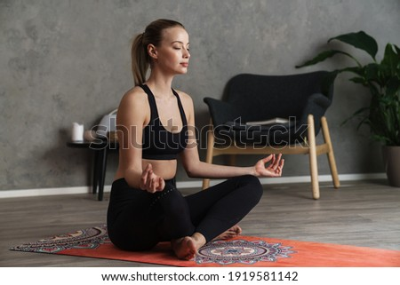 Attractive young healthy woman practising yoga on a mat in the studio, in a yoga position