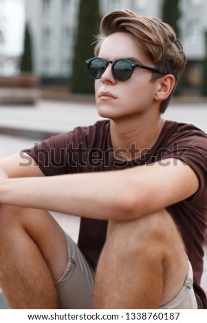 Attractive young hipster man in light shorts in stylish sunglasses with a stylish hairstyle in a trendy T-shirt sits on the vintage steps in the city. Urban american guy outdoors. Summer fashion.