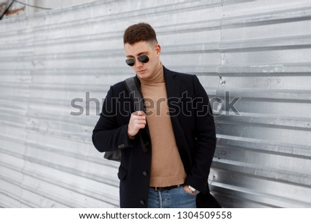 Attractive young hipster man stylish sunglasses with a stylish hairstyle in a vintage knitted sweater with a backpack in a trendy coat in a jeans near a metal fence. Guy travels in the autumn day.