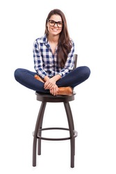 Attractive young Hispanic girl sitting on a chair with her feet up and smiling