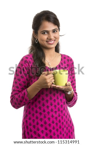 Attractive young Indian woman is showing green cup of aroma tea over white background