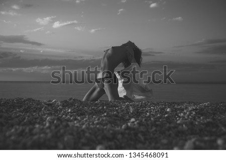 Attractive young lady suntanning nude, nudist, enjoy last sun rays. Girl sexy, topless, naked breasts with wild hair at seashore at sunset. Erotic concept. Woman stands on knees on beach in evening. #1345468091