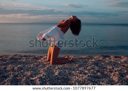 Attractive young lady suntanning nude, nudist, enjoy last sun rays. Woman stands on knees on beach in evening. Girl sexy, topless, naked breasts with wild hair at seashore at sunset. Erotic concept. #1077897677