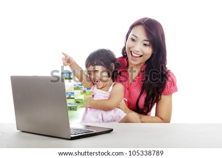 Attractive young little girl and her mother looking at family photos on the laptop