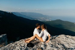 Attractive young loving couple of man in white shirt and blue jeans with girl in dress on sunny outdoor background in the green mountain landscape