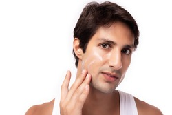 Attractive young man apply moisturizer, cream face or sunscreen on beauty face for nourishing face skin, protecting from sunlight Cool guy has nice facial skin because he look after himself well