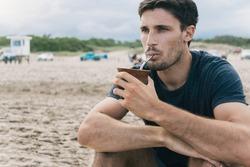 Attractive young man drinking yerba mate, herbal tea.