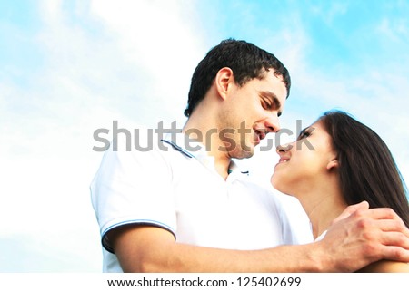 Attractive young man embracing woman against blue cloudy sky