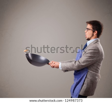 Attractive young man holding a black frying pan