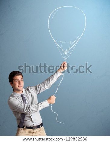 Attractive young man holding balloon drawing
