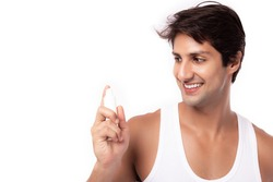 Attractive young man holding moisturizer, cream face or sunscreen bottle for nourishing face skin, protecting from sunlight with satisfied product, smile face. Handsome guy has nice facial skin
