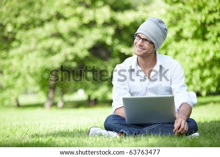 Attractive young man in a hat with a laptop outdoors