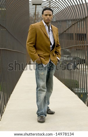 Attractive young man in a suit and jeans on a bridge.