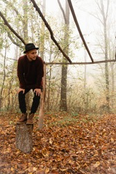 Attractive young man in red sweater and black hat crouched on the stump under the dry log canopy among the forest in fog, autumn time