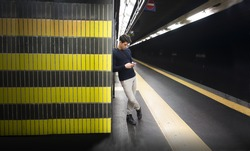 Attractive young man in train or underground station using cellphone (mobile)