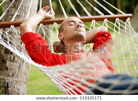 Attractive young man laying down on a hammock in a tropical home's garden, relaxing.