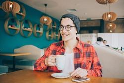Attractive young man or freelancer is sitting in cafe and drinking tea. Smiling guy holding cup in his left hand and waiting for friends.