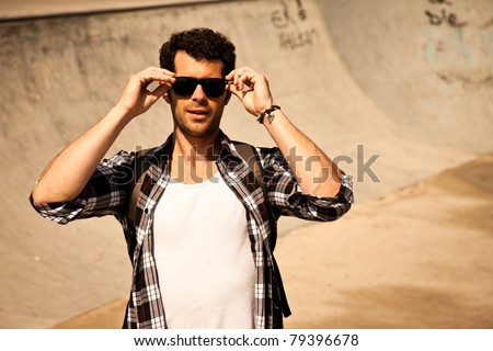 Attractive young man putting on his sunglasses.