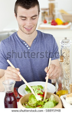 Attractive young man putting salad on a plate in the ktichen