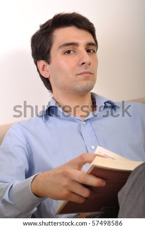 attractive young man reading a business book on the couch
