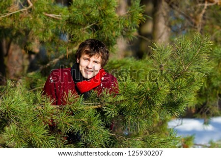 Attractive young man smiling in winter forest