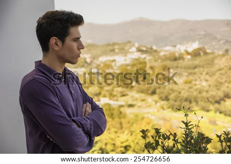 Attractive young man standing with folded arms looking over a rural landscape with a distant village with a serious expression
