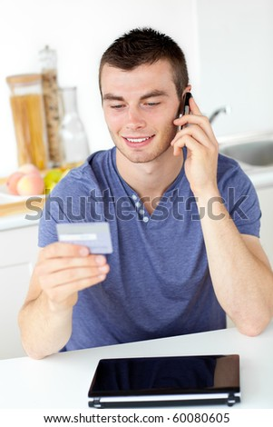 Attractive young man talking on phone holding a card in the kitchen at home