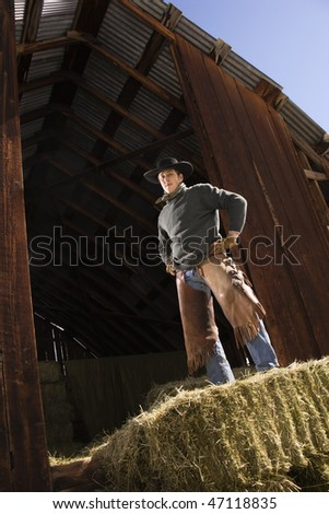 Attractive young man wearing a cowboy hat while standing confidently on top of hay bales. Vertical shot.